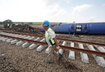 A railway worker walks at the scene where a passenger train derailed on Sunday, near Corlu in Tekirdag province