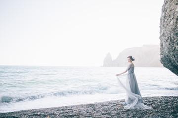 Beautiful young woman bride in long dress near the sea.