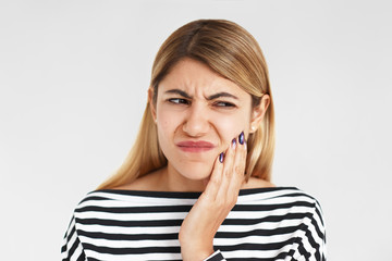 People, bad health condition and sickness concept. Studio shot of beautiful young Caucasian female having painful facial expression, pressing hand against her cheek while suffering from toothache
