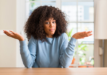 African american woman at home clueless and confused expression with arms and hands raised. Doubt concept.