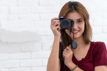 Beautiful cheerful young woman holding camera and focusing on you with smile while standing against white background. Portrait of a photographer covering her face with the camera.