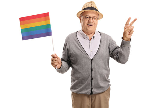 Mature man holding a rainbow flag and making a peace gesture