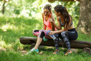 Two young woman sitting at the park and relaxing after jogging outdoor.They talking and laughing.