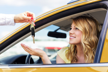 An attractive woman in a car gets the car keys. Rent or purchase of auto.