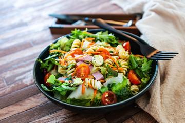 Salad with fusilli pasta accompanied tomatoes, mozzarella, smoked ham and italian cheese