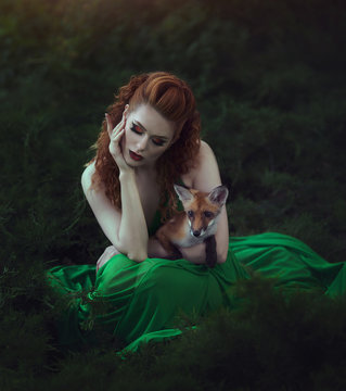 A red-haired girl in a green dress is sitting with a fox in a fairy forest. Beautiful young woman with a young fox.