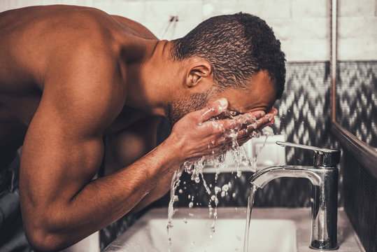 Young Afro-American Man Washing Face in Bathroom.