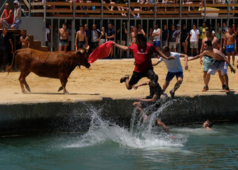 """Revellers chasing a bull jump into the sea during the """"Bous a la Mar"""" festival in the coastal town of Denia"""