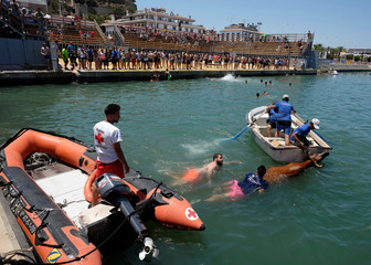 """Revellers on a boat tow a bull to safety during the """"Bous a la Mar"""" festival in the coastal town of Denia"""