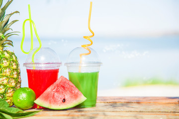 Bright Fresh healthy juices, fruit, pineapple, watermelon on the background of the sea. Summer, rest, healthy lifestyle Copyspace