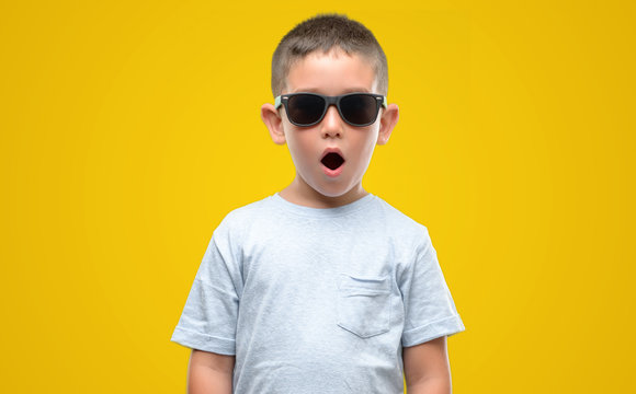 Dark haired little child wearing sunglasses scared in shock with a surprise face, afraid and excited with fear expression