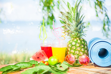 Bright Fresh healthy juices, fruit, pineapple, watermelon. sunglasses yoga mat on the background of the sea. Summer, rest, healthy lifestyle Copy space
