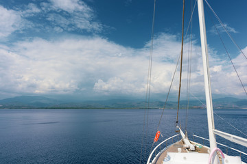 A sea voyage on a yacht. Island and cloudy sky in the background