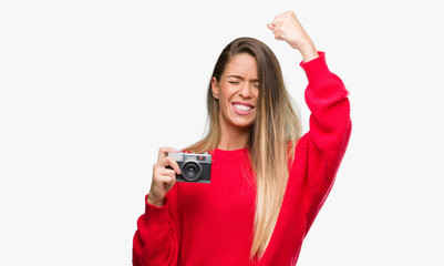 Beautiful young woman holding vintage camera annoyed and frustrated shouting with anger, crazy and yelling with raised hand, anger concept