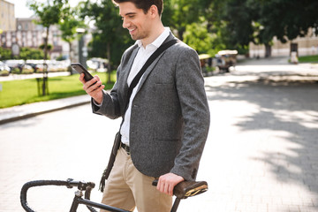 Happy young businessman using mobile phone