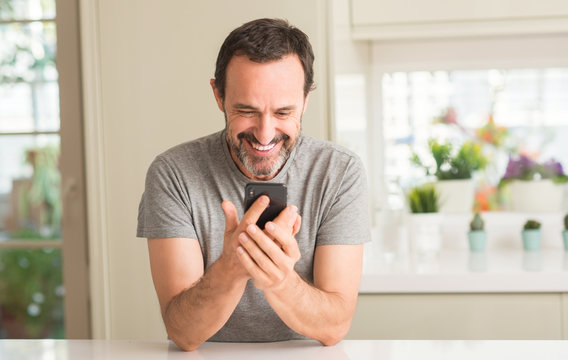 Middle age man using smartphone with a happy face standing and smiling with a confident smile showing teeth