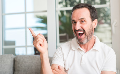 Handsome middle age man very happy pointing with hand and finger to the side