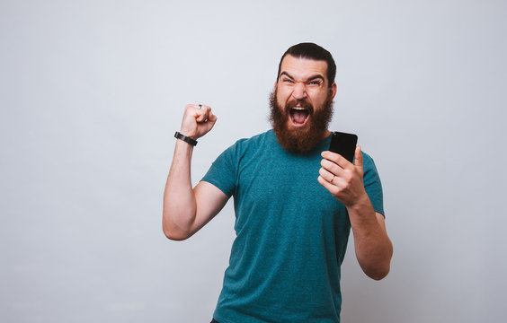 Bearded man, winner eith smartphone in hand screaming on white background.