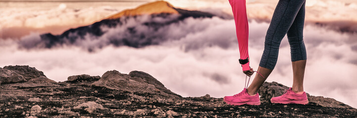 Runner woman getting ready for trail run in volcano altitude mountains background tying up running shoes laces. Fitness and sports motivation healthy lifestyle. Banner panorama.