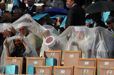 Muftis take cover from the rain as they wait for arrival of Turkish President Erdogan during a ceremony at the Presidential Palace in Ankara