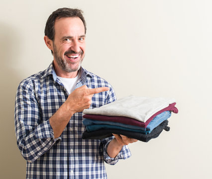 Senior man holding folded laundry clothes very happy pointing with hand and finger to the side