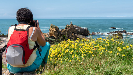 woman take picture from Rock of the Virgin, Biarritz city, France