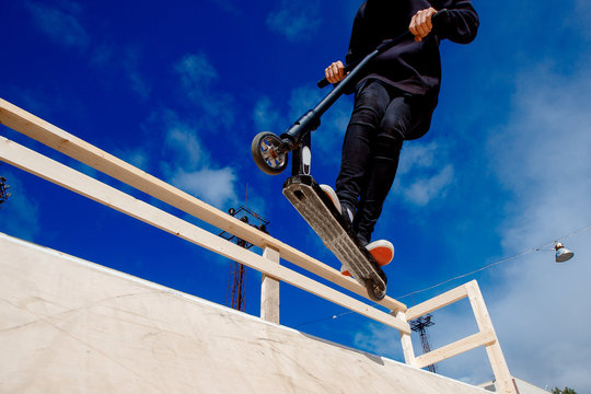 Man riding kick scooter in park ramp and springboards. Background Blue sky