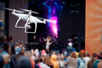 Drone of white color shoots recording concert, in background appears singer. Concept video technology.