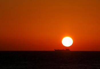 A cargo ship steams on the Atlantic Ocean as the sun sets near Zahora