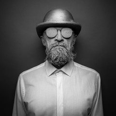 Portrait of a bearded man in with sunglasses. The face is covered with clay
