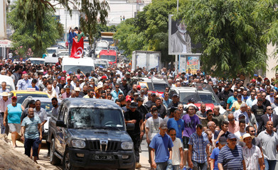 People walk beside the ambulance transporting the coffin of Anis El Werghi, a Tunisian security forces member, who was killed in an ambush in the northwest of the country, during his funeral in Tunis