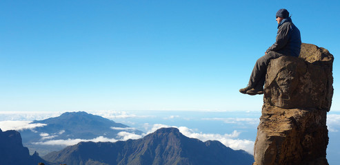 Resting man sitting on the rock above the crater Caldera de Taburiente, Island of La Palma, Canary Islands, Spain