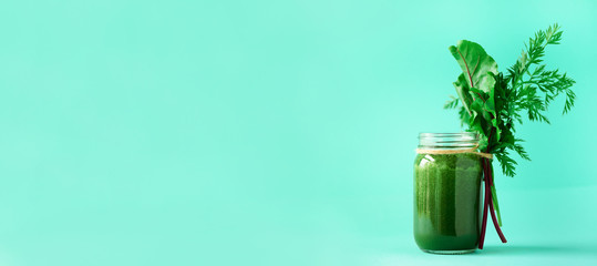 Banner of green smoothie with leafy beet greens and carrot tops on blue background, copy space. Summer vegan food concept. Healthy detox diet. Fresh squeezed juice, drink from vegetables.