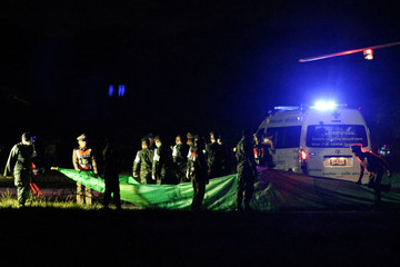 Rescued schoolboys are moved from a military helicopter to an awaiting ambulance at a military airport in Chiang Rai