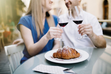 Cheerful couple in a restaurant with glasses of red wine.  Young couple with glasses of red wine in a restaurant with city view