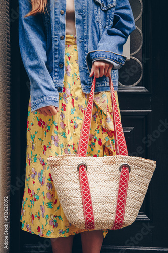 5f18cc8728a street style fashion details. woman in denim jacket and floral dress  holding a straw purse. perfect summer fashion accessories.