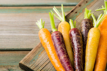 Fresh raw colorful carrots roots, purple, yellow and orange on old wooden table. Healthy food vegetable background with copy space.