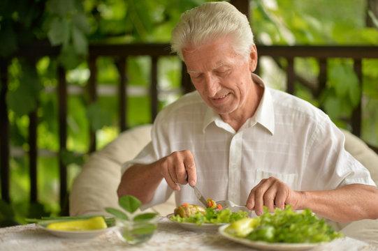 Portrait of handsome senior man eating
