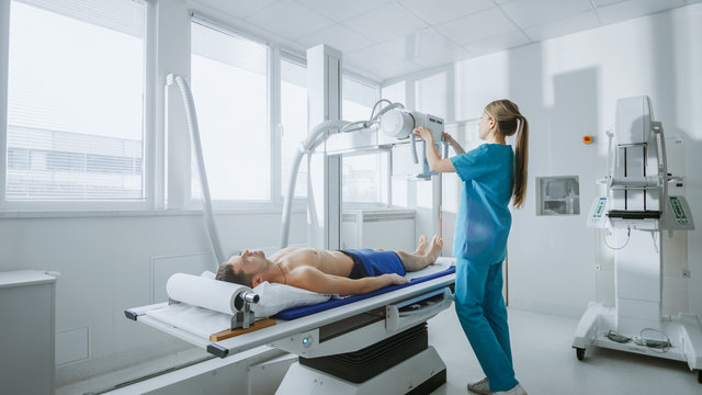 In the Hospital, Low Angle Shot of Man Lying on a Bed, Female Technician adjusts X-Ray Machine. Scanning for Fractures, Broken Limbs, Injuries, Cancer or Tumor. Modern Hospital.