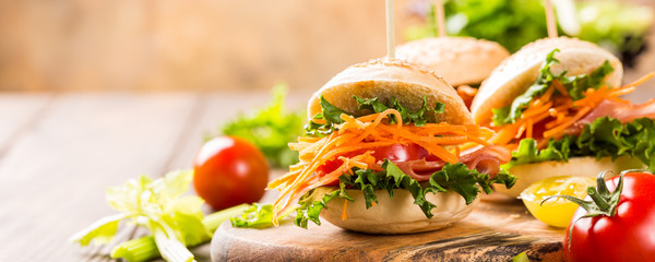 Homemade mini burgers with ham, tomato, carrot, fresh salad served on wooden board. Healthy junk food concept with copy space. Banner.