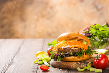 Homemade bagel burger with beef,tomato, carrot, fresh salad on wooden background. Unhealthy junk food concept with copy space.