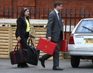 Officials carry government red boxes from the official residence of the Foreign Secretary in London