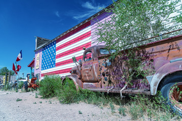Fotobehang Route 66 SELIGMAN, AZ - JUNE 29, 2018: Old truck and american flag along Route 66. This is the most famous historic route in the US