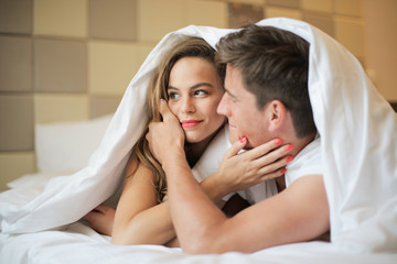 Couple in bed in a hotel.