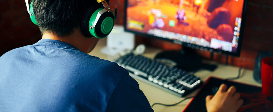 young man playing game on computer, banner