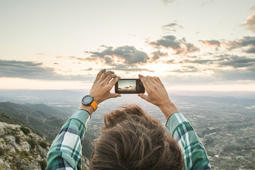 Guy taking a picture with the mobile phone to a valley