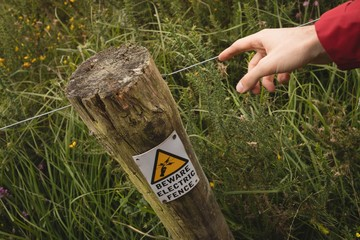Close up of man's hand touching electric fence