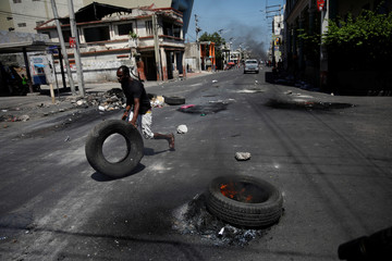A man pushes a tire next to the burning tires on a street of Port-au-Prince