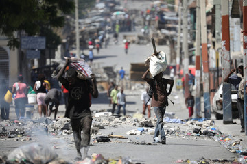 Men carry bags along a blocked street in Port-au-Prince