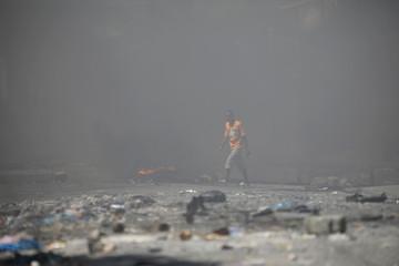 A man walks amid smoke along a blocked street in Port-au-Prince